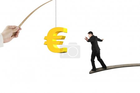 Man balancing golden euro symbol fishing lure isolated on white