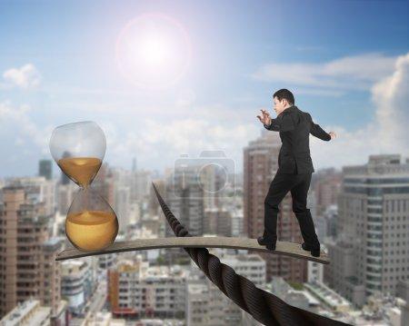 Photo pour Homme d'affaires et sablier doré sur panneau de bois, équilibrage sur fil, avec ciel soleil paysage urbain fond . - image libre de droit