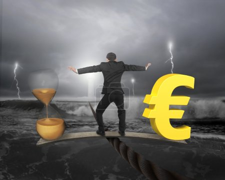 Photo for Man standing on wood board between hourglass and golden euro sign, balancing on wire, with dark stormy ocean background. Time is money concept. - Royalty Free Image