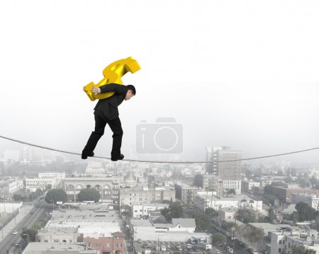 Businessman carrying golden dollar sign balancing on tightrope