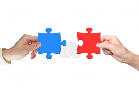 Two hands assembling jigsaw puzzle pieces