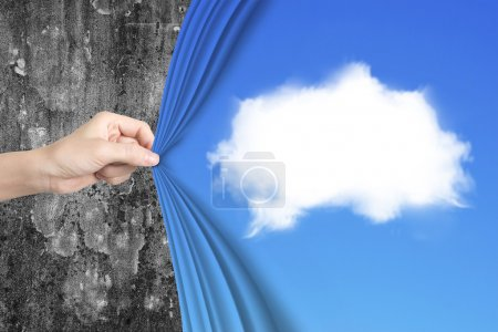 Woman hand pulling white cloud blue curtain covering old wall