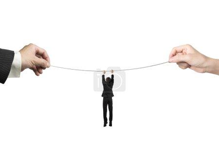Photo pour Homme d'affaires accroché sur la corde raide avec des mains d'homme et une femme tenant deux côtés, isolées sur blanc. - image libre de droit