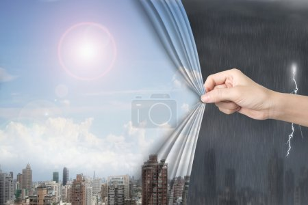 Woman hand pulling sunny sky cityscapes curtain covering stormy