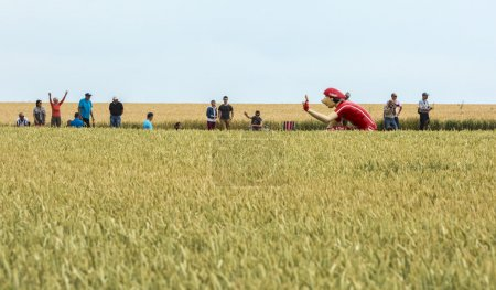 Photo pour Quievy,France - July 07, 2015: Vittel mascot in a wheat field, during the passing of the Publicity Caravan on a cobblestone road in the stage 4 of Le Tour de France on July 7 2015 in Quievy, France. - image libre de droit