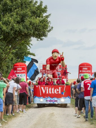 Photo pour Quievy,France - July 07, 2015: Vittel vehicle during the passing of the Publicity Caravan on a cobblestone road in the stage 4 of Le Tour de France on July 7 2015 in Quievy, France. - image libre de droit