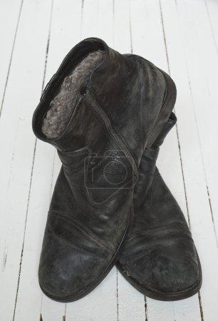 Photo pour Vieille botte noire sur plancher de bois blanc - image libre de droit