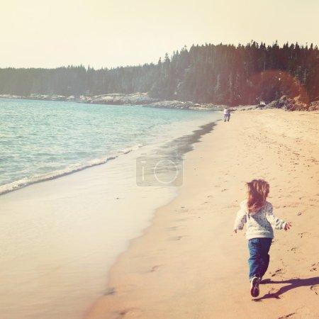 Little girl runs on beach