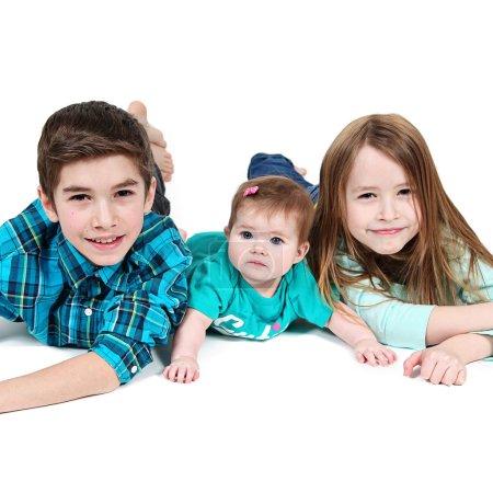 Photo pour Trois enfants posant dans Studio. Petit garçon et ses sœurs couchés sur le sol, isolés sur blanc - image libre de droit