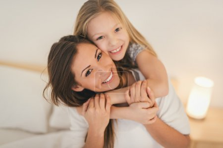 Photo for Beautiful smiling mother and her daughter hugging in bed. They are sitting on bed at pajamas and smiling looking at camera. - Royalty Free Image
