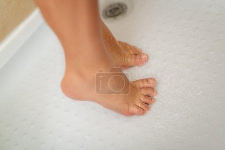 Photo pour Gros plan d'une femme méconnaissable qui entre dans la douche. Concentration sélective . - image libre de droit