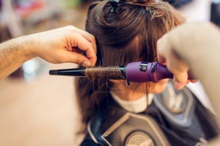 Photo pour Gros plan d'un coiffeur masculin faisant des boucles à de longs cheveux bruns avec des fers à friser . - image libre de droit