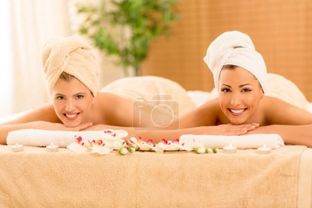 Photo for Two cute young women enjoying during a skin care treatment at a spa. Looking at camera. - Royalty Free Image