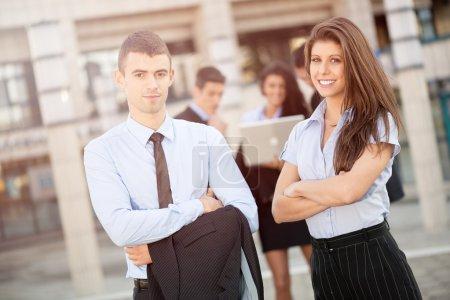 Foto de Joven pareja de negocios de éxito con su equipo de negocios en el fondo, de pie frente a los edificios de oficinas y con una sonrisa mirando a la cámara . - Imagen libre de derechos