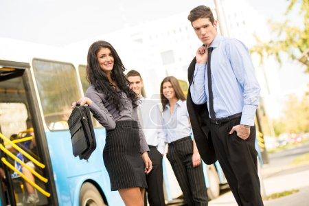 Junge Geschäftsleute warten auf den Stadtbus