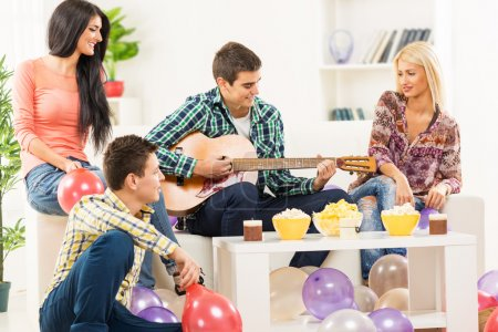 Photo pour A small group of young people, friends at home party. A young man sitting on the couch between two beautiful girls, playing acoustic guitar and a guy sitting on the floor next to the stool - image libre de droit