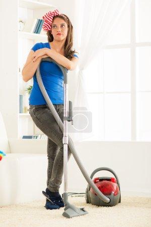 Photo pour Un penchant debout de jeune femme au foyer sur aspirateur fatigué du travail domestique. - image libre de droit