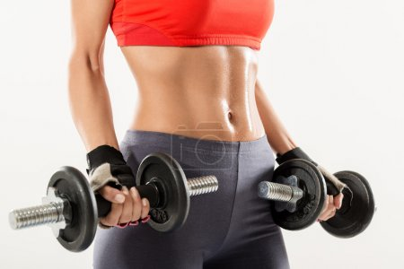 Photo for Close-up of the perfect woman body with dumbbells - Royalty Free Image