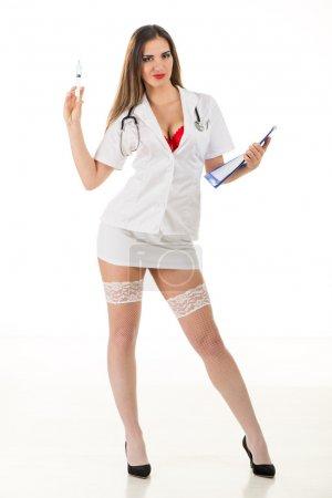 Photo pour Belle infirmière sexy souriante debout et tenant des injections sur fond blanc. Regardant la caméra . - image libre de droit