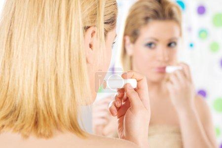 Photo pour Gros plan de belle fille aux yeux bleus appliquant du baume sur les lèvres devant le miroir dans sa salle de bain le matin. Vue arrière . - image libre de droit