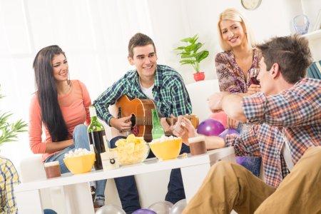 Photo pour Un petit groupe de jeunes traînent à la fête de la maison, bavardant entre eux pendant que leur ami s'amuse à jouer de la guitare acoustique . - image libre de droit