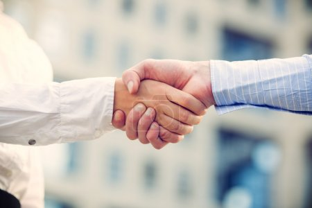 Photo for Hands of businessman and businesswoman shaking hands, while in the background looms office building. - Royalty Free Image