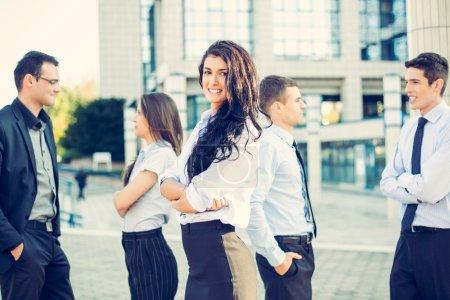 Photo pour Portrait d'une femme d'affaires jeune et beau avec son équipe jeunes gens d'affaires en face de l'immeuble de bureaux. - image libre de droit