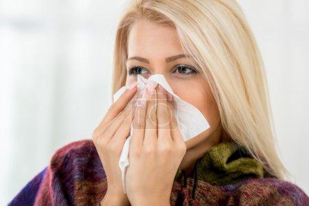 Photo pour Une belle fille tenant un mouchoir à son nez . - image libre de droit