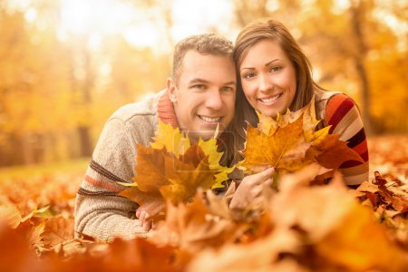 Photo for Beautiful young couple in sunny forest in autumn colors. They are lying on the fall meadow at embraced and holding yellow leaves. Looking at camera. - Royalty Free Image