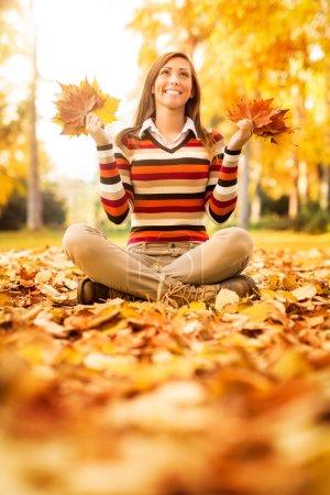 Photo pour Jeune femme mignonne appréciant dans la forêt ensoleillée dans les couleurs d'automne. Elle tient des feuilles jaunes dorées . - image libre de droit