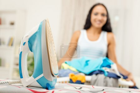 Photo for Close-up of a iron on ironing board. In background standing young woman with basket laundry. Selective focus. - Royalty Free Image