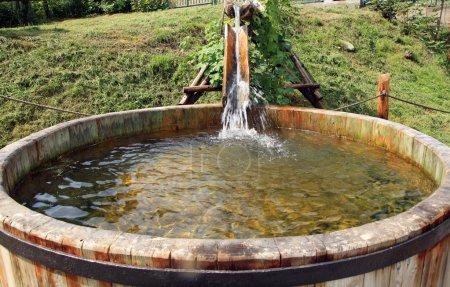 Photo pour Réservoirs d'eau en bois coulant. Décoration jardin irrigation . - image libre de droit