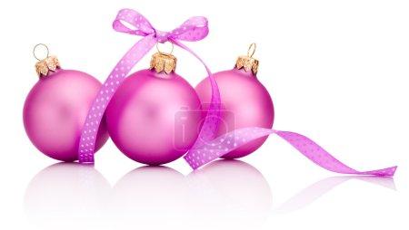 Photo pour Trois billes roses de Noel avec l'arc de ruban d'isolement sur le fond blanc - image libre de droit