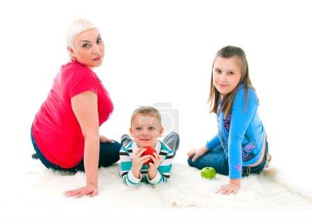 Foto de Joven madre con dos hijos en un fondo blanco - Imagen libre de derechos