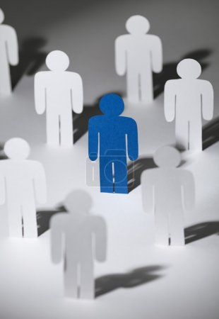 Group of similar paper men with a blue one