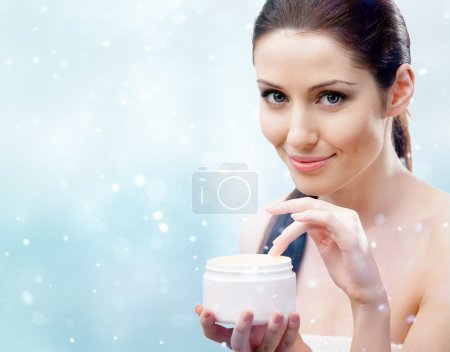 Woman starting to apply moisturizing mask