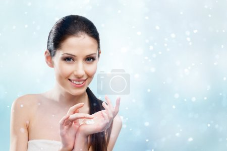 Woman starting to apply protective winter cream