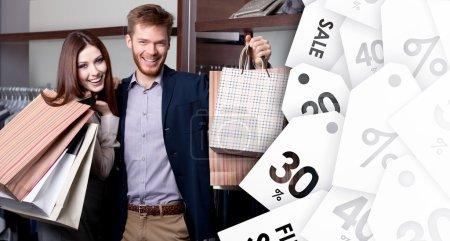 Photo pour Couple joyeux montrant leurs achats après les achats en vente - image libre de droit