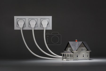 Photo for Concept of increased consumption of electricity - small house on grey background - Royalty Free Image