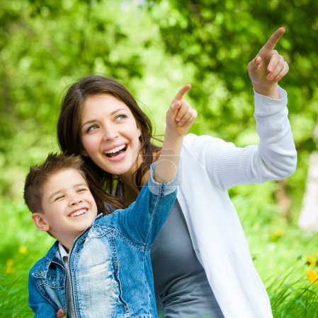 Photo for Mother and her son sitting on grass and pointing hand gesture in park. Concept of happy family relations and carefree leisure time - Royalty Free Image