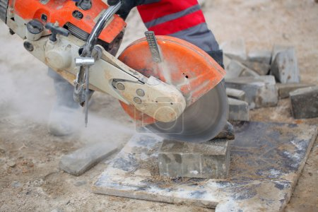 Construction worker using concrete saw