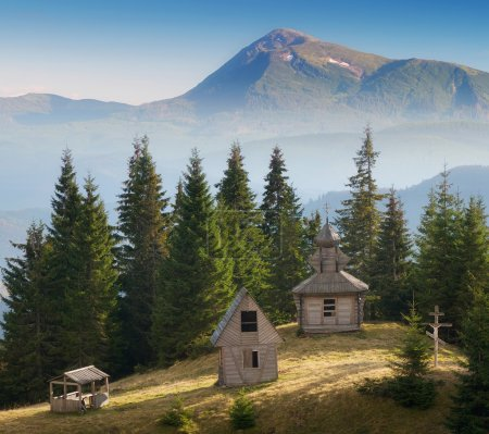 Photo pour Sunny meadow with old wooden church. Mountain landscape with religious buildings - image libre de droit