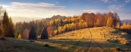 Foto de Autumn landscape with haystacks. Evening in a mountain village. Carpathian mountains, Ukraine, Europe - Imagen libre de derechos