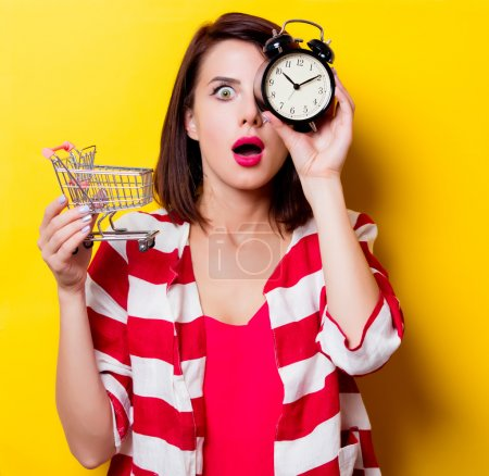 young woman with cart and alarm clock