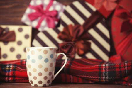 Winter tea in a cup and christmas gifts on background.