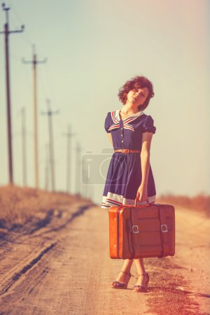 Beautiful brunette girl with suitcase on the field