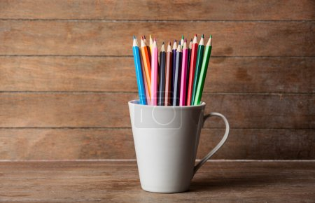 Color pencil in cup on a wooden background