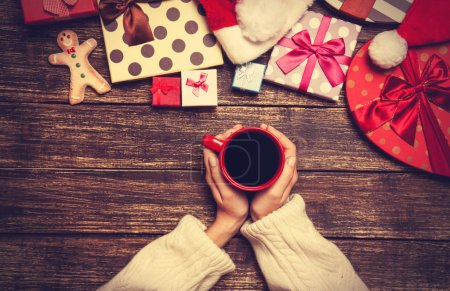 Female holding cup of coffee on wooden table near christmas gift