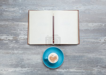 Book and cup of coffee on wooden table.