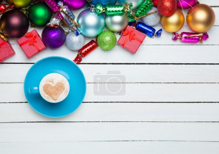 Coffee cup and christmas toys on white background.